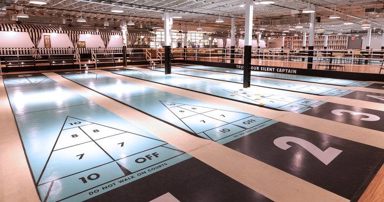 shuffleboard courts in a giant warehouse