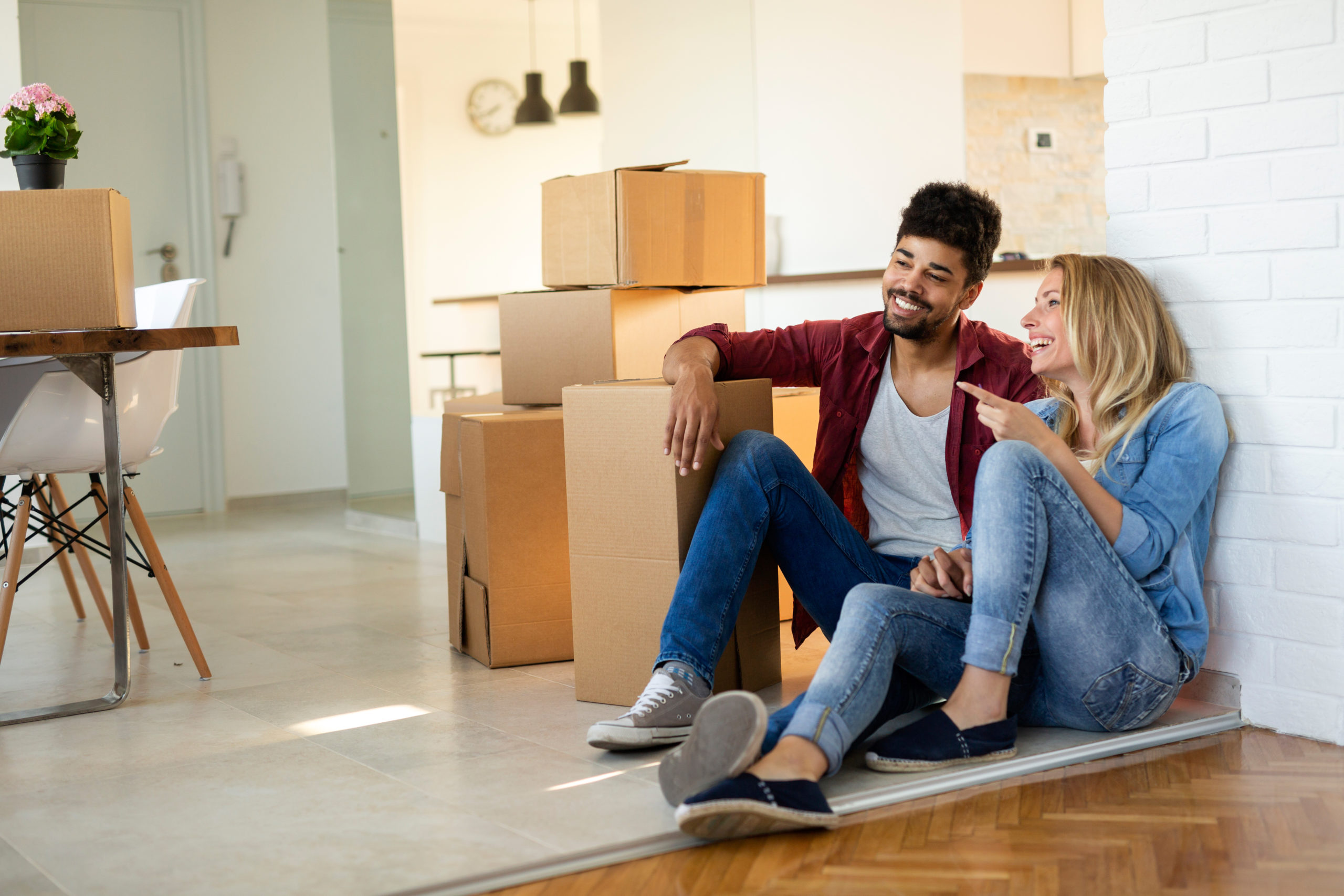 young couple sitting with moving boxes