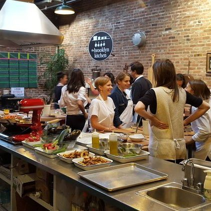 People socializing while taking a cooking class at the Brooklyn Kitchen
