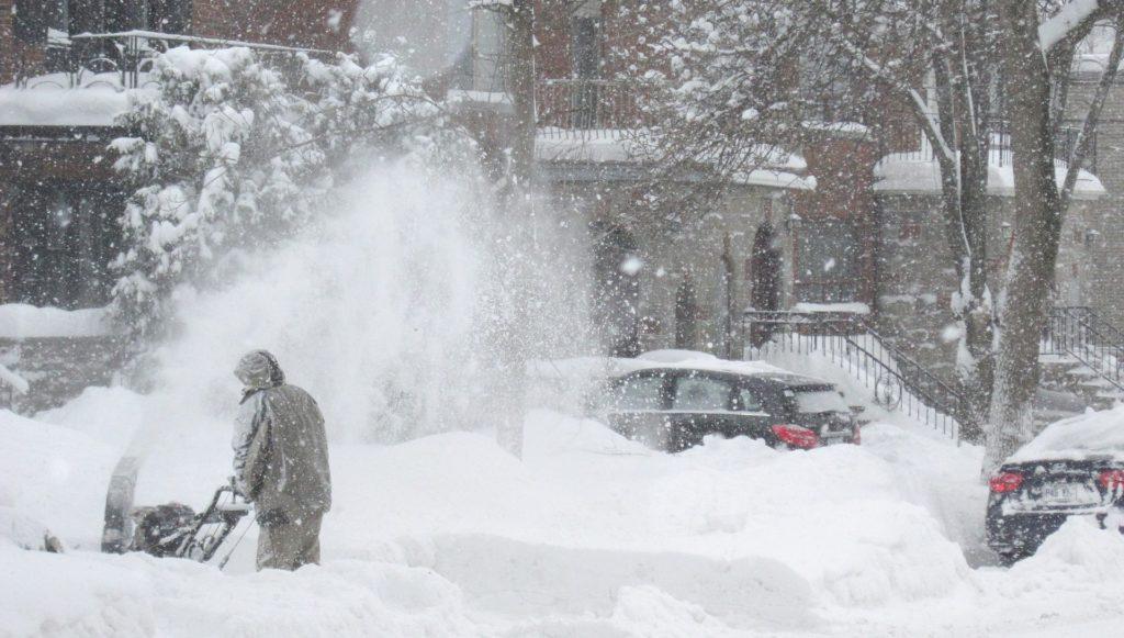 man snow blowing walkway during snowstorm